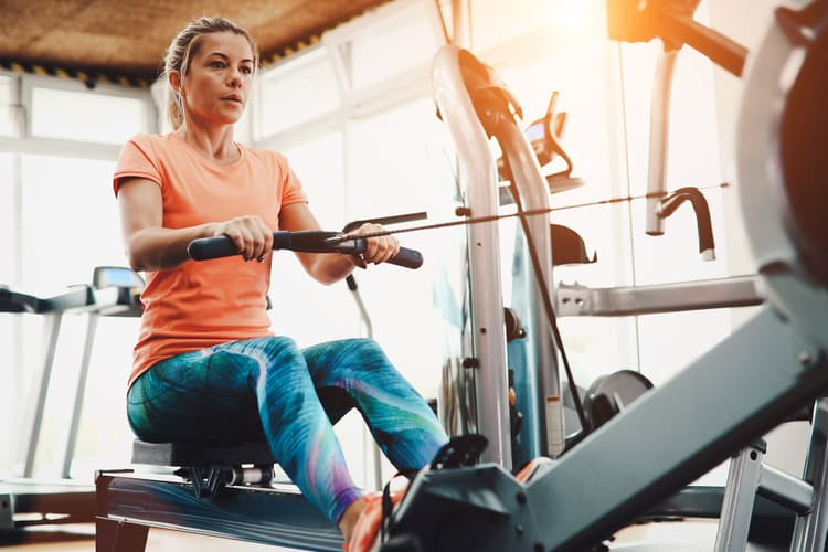 photo of woman using row machine in gym