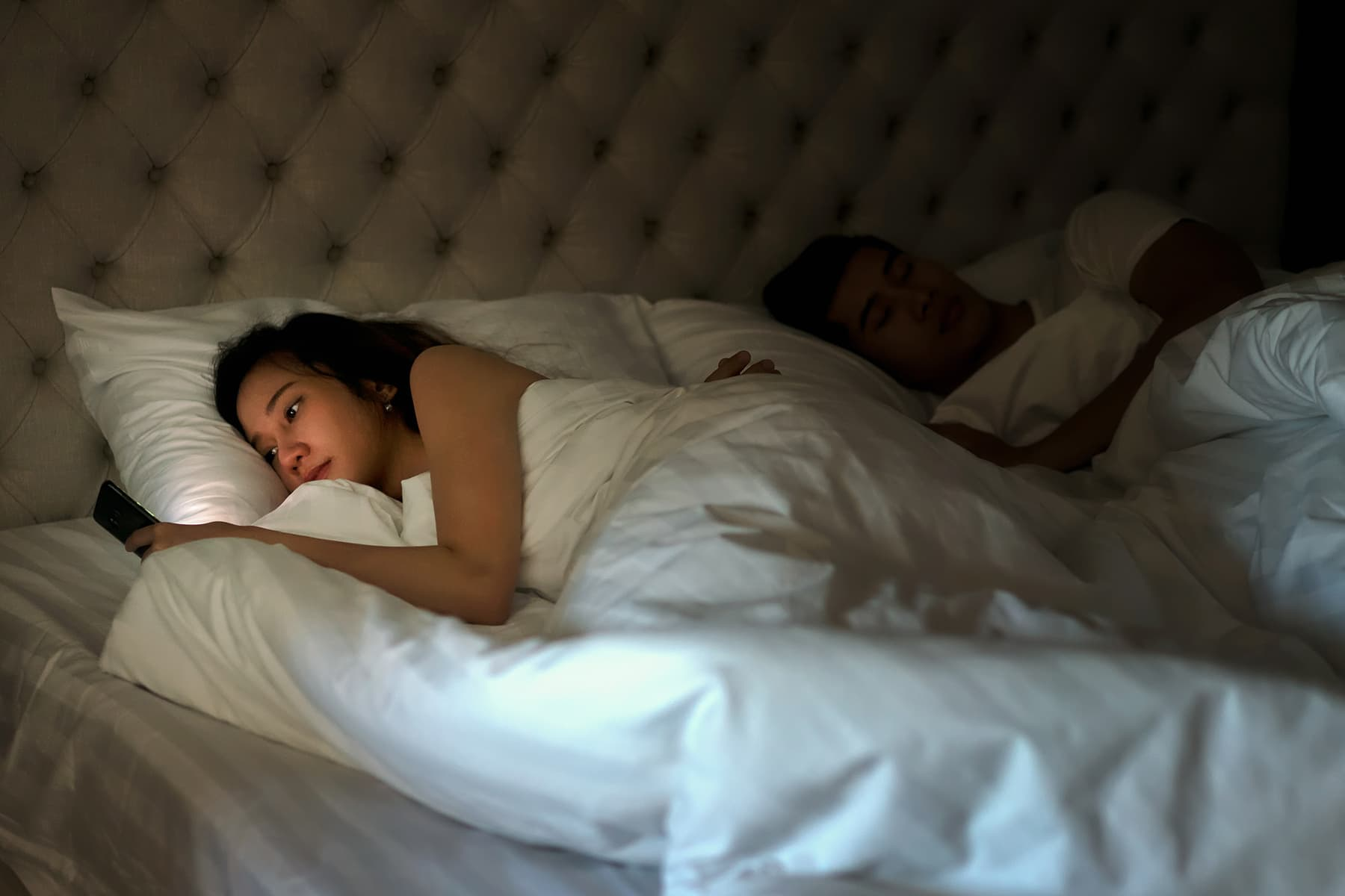 photo of woman using smartphone in bed