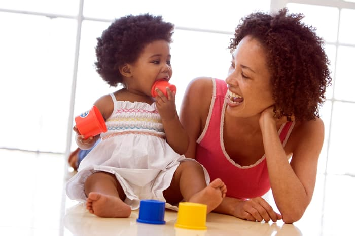 photo of mother playing with infant daughter