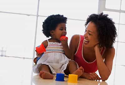 Mother and daughter indoors playing