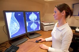 photo of radiation technician reviewing mammograph