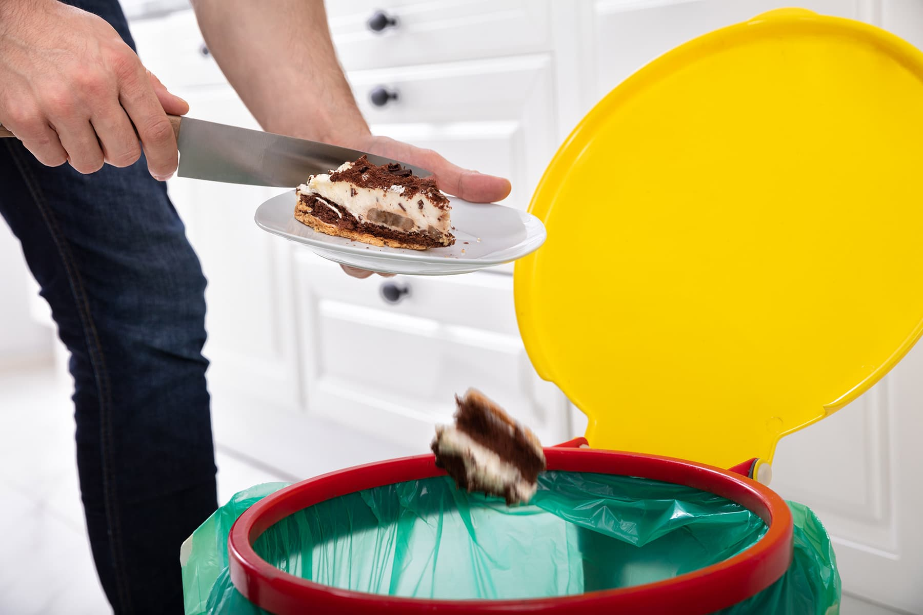 photo of disposing of cake in kitchen trash can