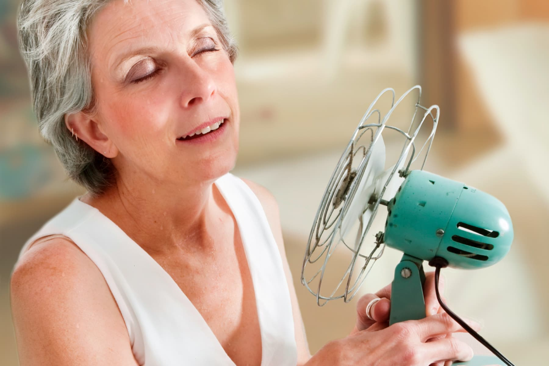 woman using fan to cool