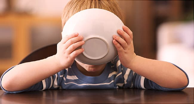 boy drinking from cereal bowl