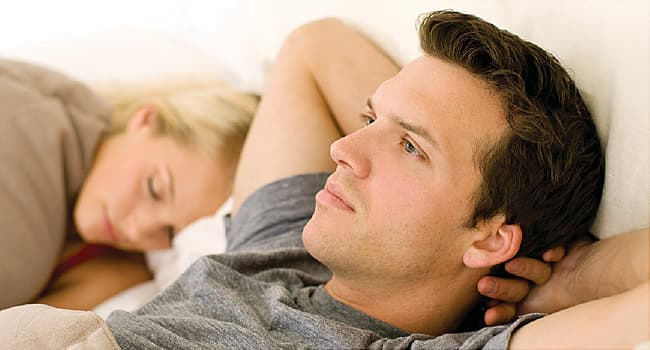man awake in bed next to sleeping woman