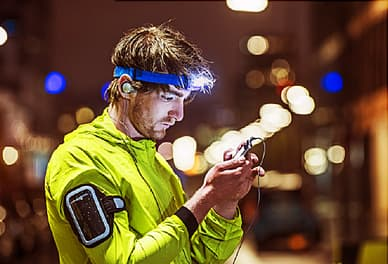 Runner looking on smartphone, wearing head torch
