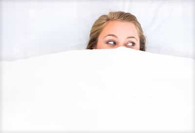 woman peeking over bed sheet