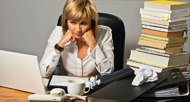 woman working at cluttered desk