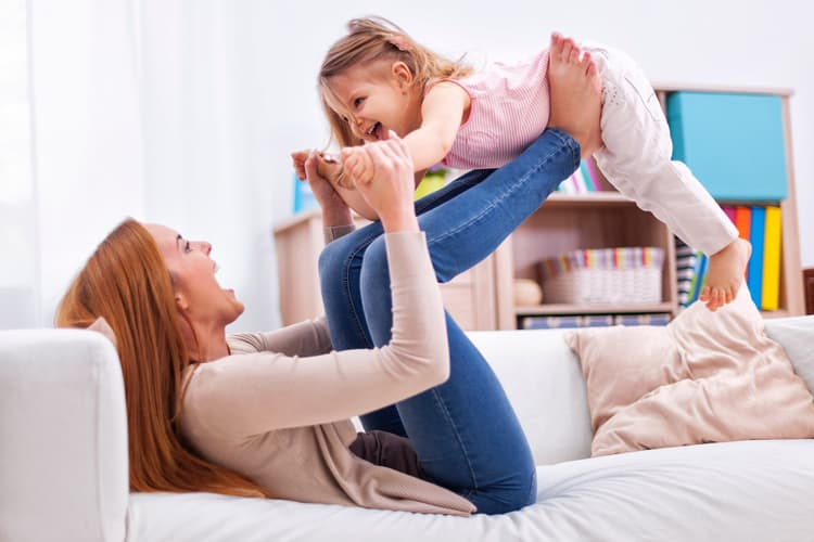 photo of mother playing with young daughter