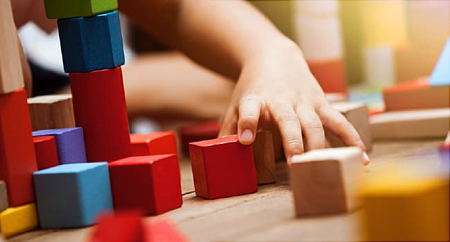 child's hand playing with blocks