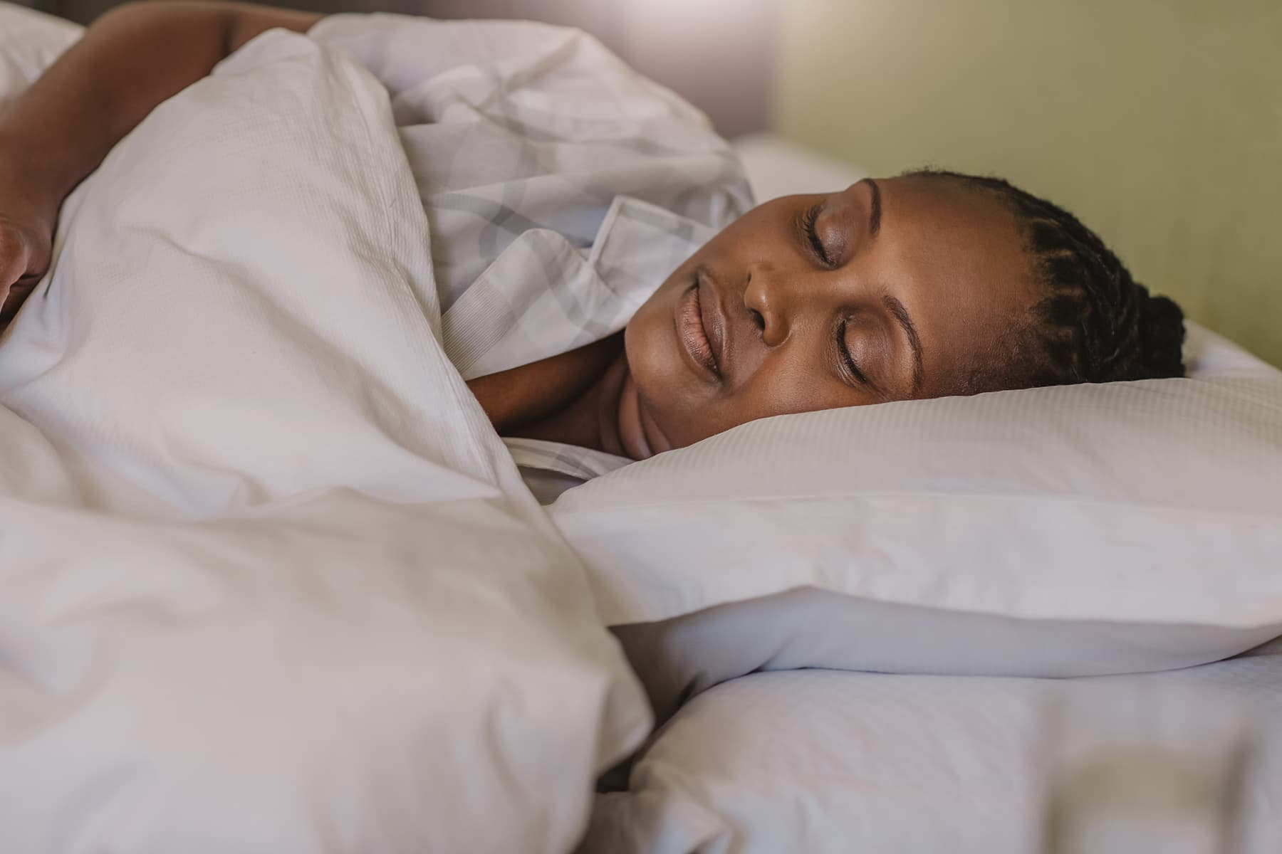 photo of woman waking up in bed