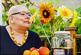 bald woman smelling flowers