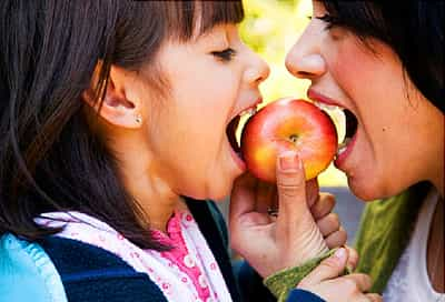 mother and daughter eating an apple