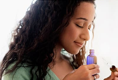 woman smelling aromatherapy bottle