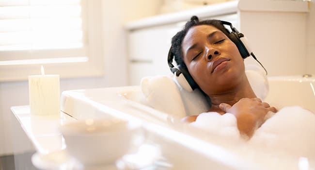 Woman with headphones taking bubble bath