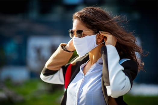 photo of woman adjusting mask as she walks in pub