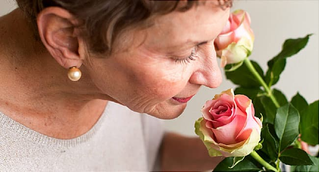 mature woman smelling roses