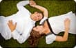 couple lying in grass holding hands