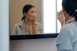 photo of woman putting on make up