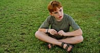 sad kid sitting in grass