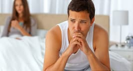 upset man sitting on edge of bed
