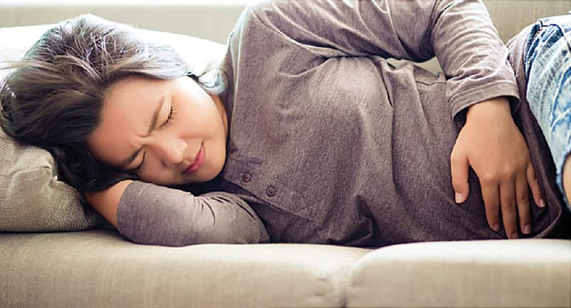 girl with stomach pain lying on couch