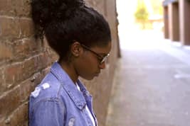 photo of woman leaning against wall