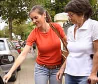 photo of woman helping mature woman into car
