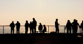 silhouettes of people at fence