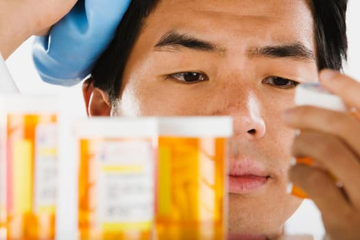 young man looking at prescription pill bottle