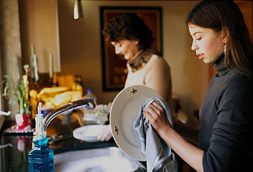 daughter helping mother with dishes