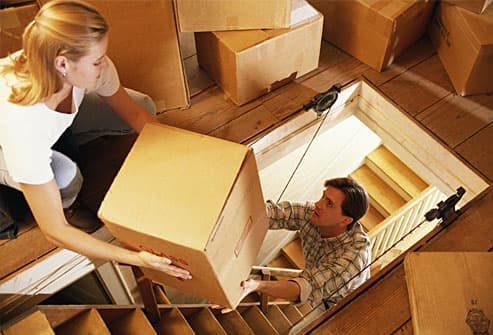 Couple moving clutter into attic