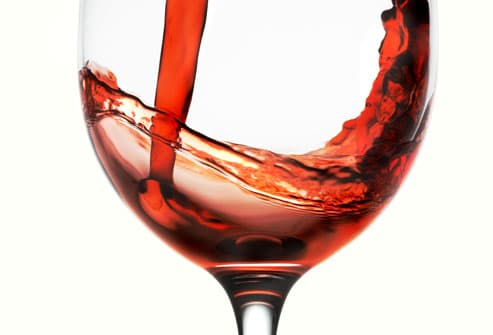 Red wine being poured into glass, close-up