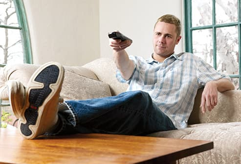 man on sofa using tv remote