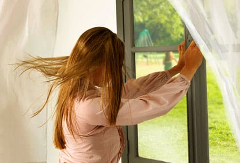 Woman closing window to shut out a strong breeze