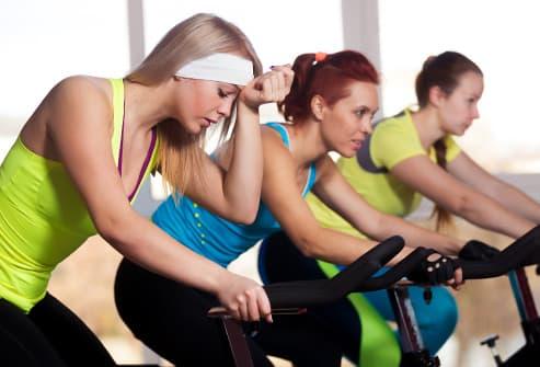 woman feeling dizzy on cycle in sports club