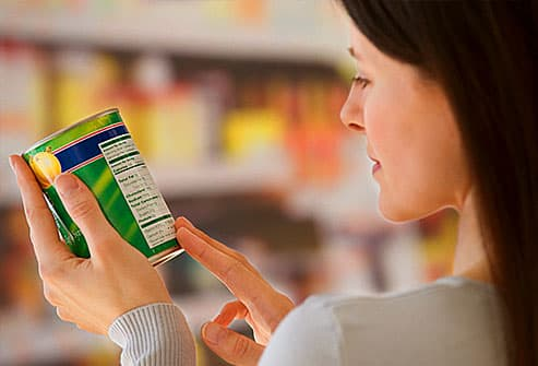 Woman reading canned veggie label