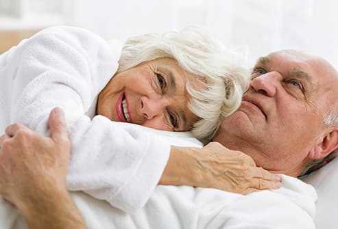 romantic senior couple lying in bed