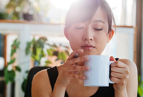 relaxed young woman with cup of coffee