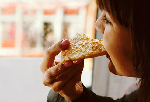 young woman eating pastry