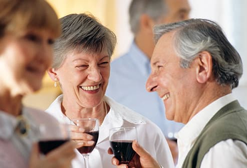 senior adults drinking red wine at party