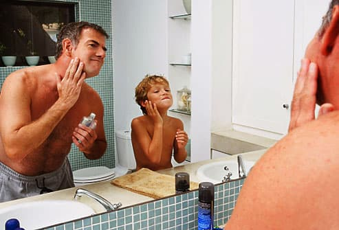 Father and son applying aftershave in mirror