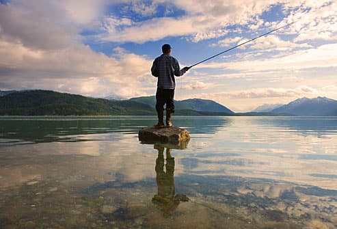 Man fishing in the middle of a scenic lake