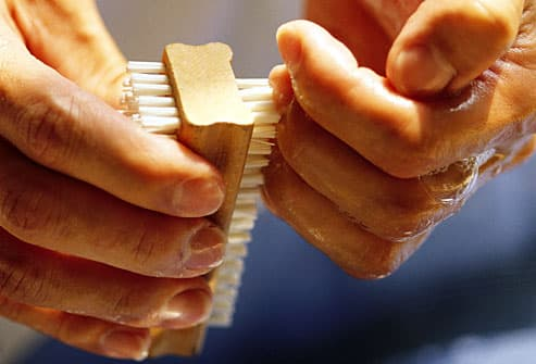 Close up of man using nail scrub brush