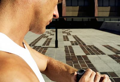 man looking at his watch before a workout