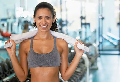 Young woman holding towel in gym
