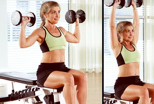 Trainer doing overhead press with free weights