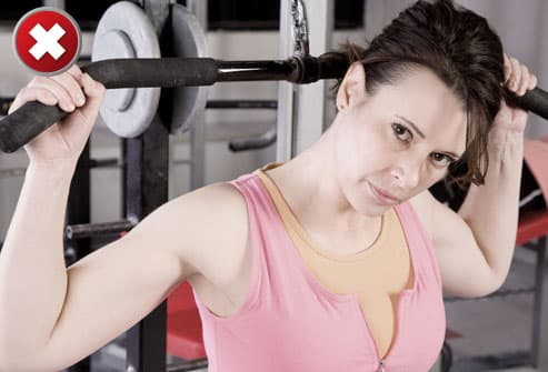 Woman doing lat pulldown behind the head