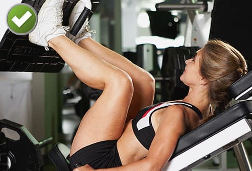 Trainer showing proper position on leg press