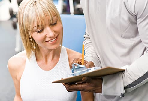 Woman at gym consulting with personal trainer